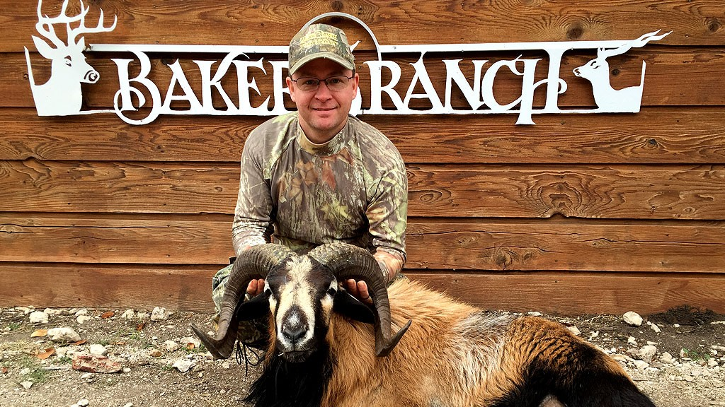 hunter during the year round exotic hunt in front of baker ranch sign