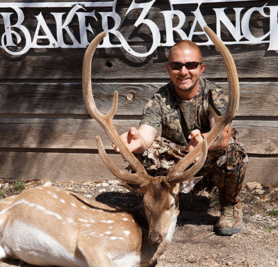 hunter during year round exotic hunt in front of baker 3 ranch sign